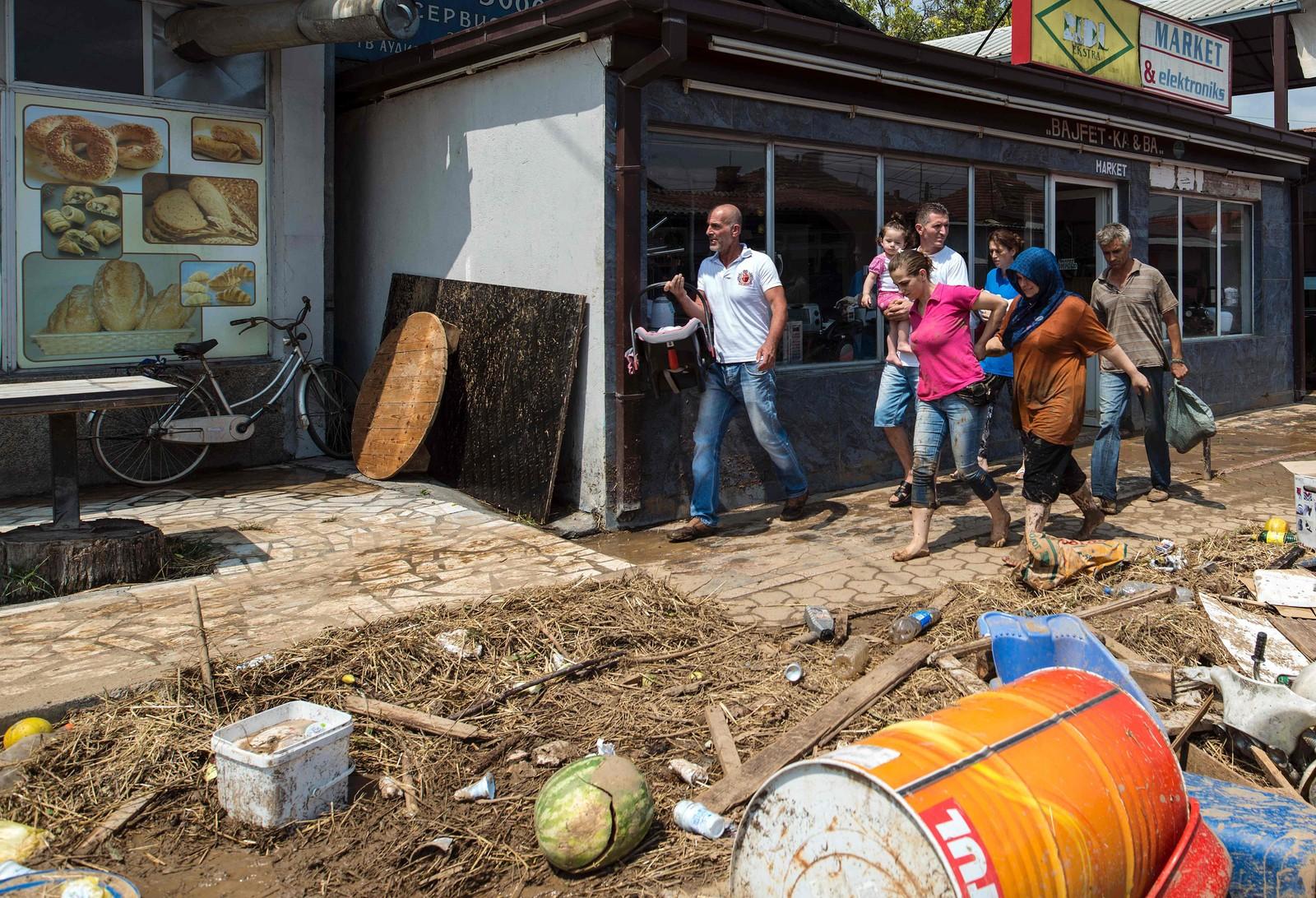 Mennesker går gjennom gjennom gater ødelagt av flommen i Stajkovci.