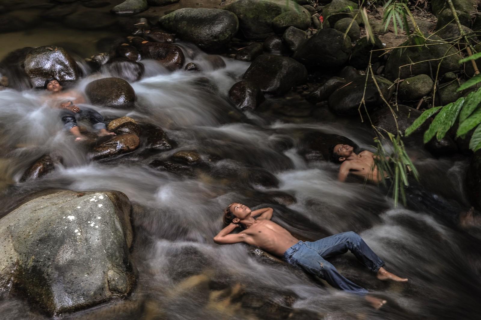 Disse ungdommene fra Hulu Langat i Malaysia kjøler seg ned i elv mens skolen deres er stengt. Malaysia, Singapore og store deler av Indonesia har i flere uker slitt med farlig røyk fra indonesiske plantasjer. Bøndene rydder land ved hjelp av ild, til tross for at dette er ulovlig. Utslippene fra disse jord- og skogbrannene gir mange innbyggere store helseproblemer.