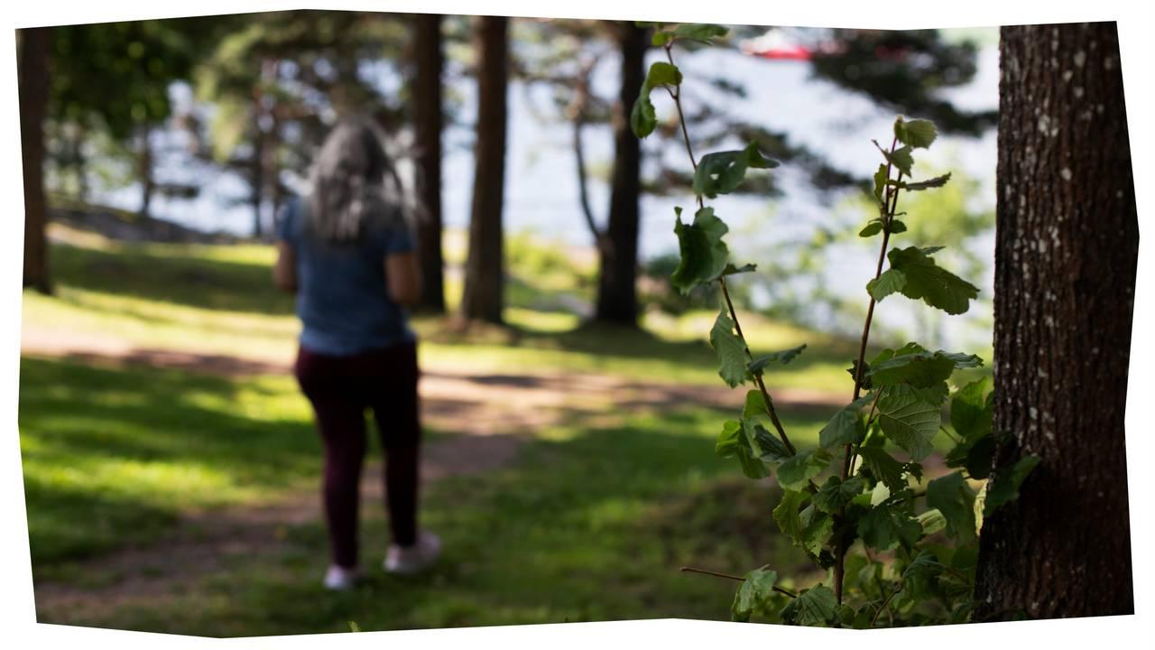 Thea går på en skogsti. Det er sol og grønt ute, i bakgrunnen skimtes et vann.