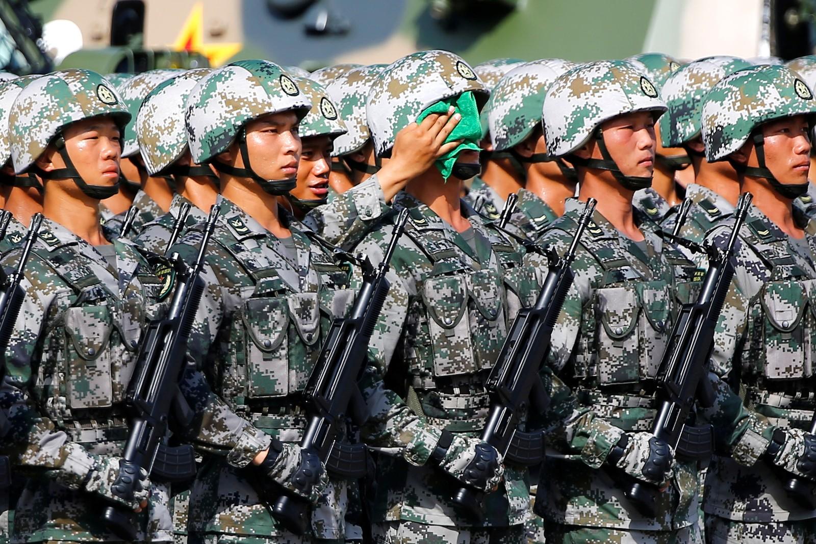 En hjelpende hånd i varmen. Disse soldatene venter på den kinesiske presidenten Xi Jinping i Hong Kong.