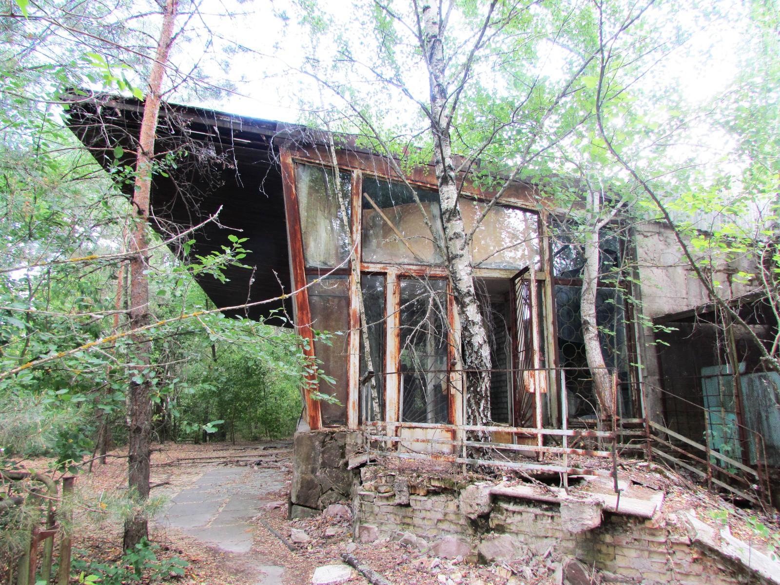 Kafe Pripyat fra bryggesiden. med knuste vinduer. Et tre har allerede vokst opp gjennom betonggulvet på terrassen.