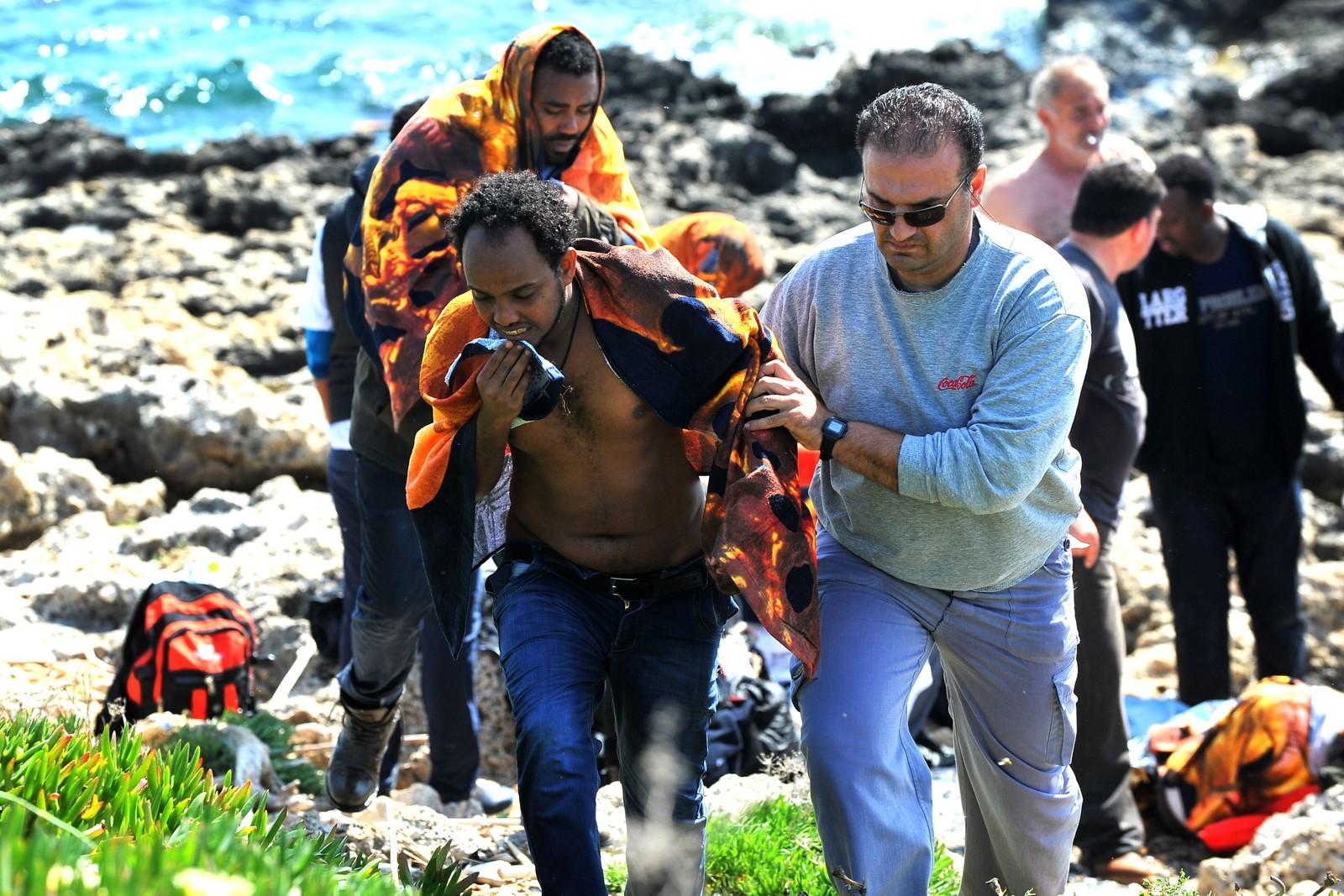 En båtflyktning hjelpes i land av en lokal greker, på Rhodos, Hellas, 20. april 2015.Bruno Gregoretti