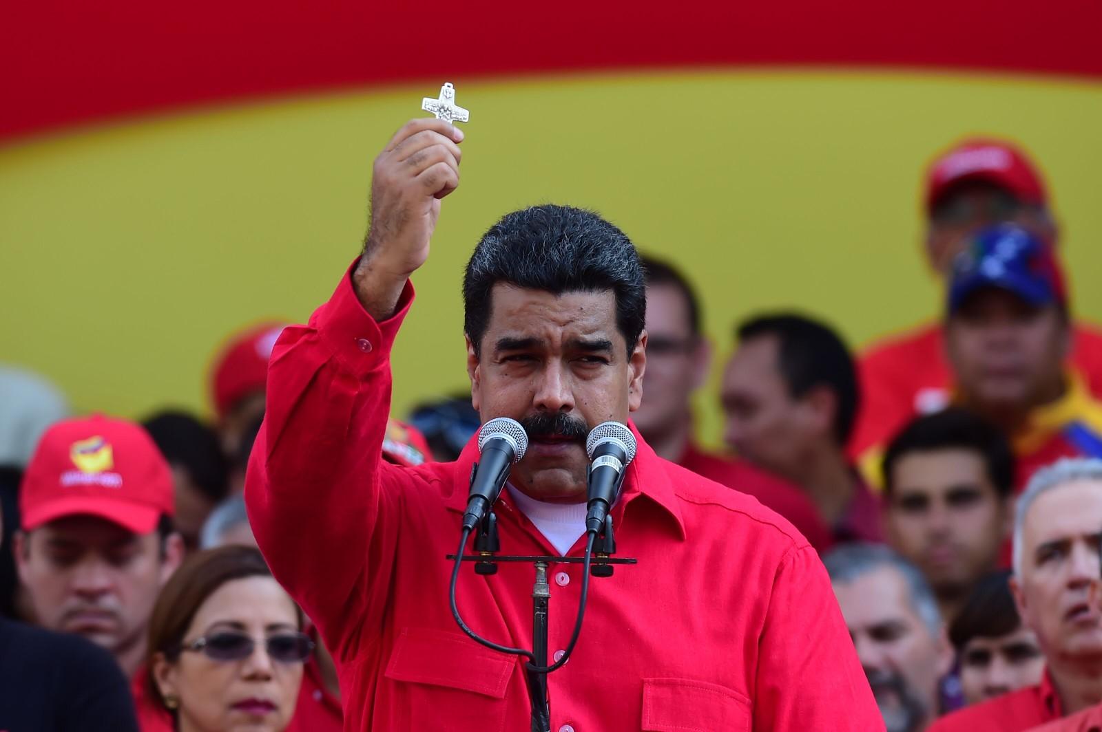 Venezuelas president Nicolas Maduro har ikke gitt opp kampen om å beholde makta på tross av krisa i landet. Her viser han et kors under en tale til sine tilhengere i hovedstaden 25. oktober.