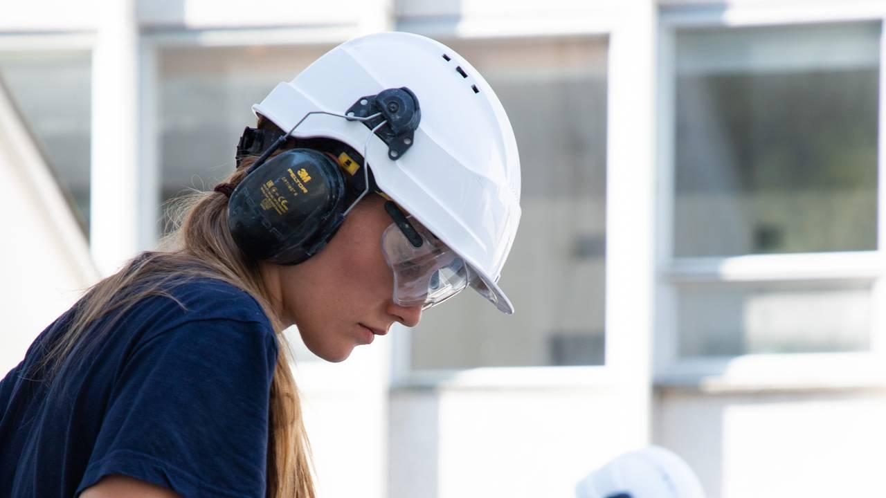 Nærbilde av Ingvild Dagsland som pusser murstein ved hjelp av meisel og skrape. Hun har på hørselvern, hjelm og vernebriller. Håret henger i hestehale på siden. I bakgrunnen skimtes søsteren, som gjør samme jobb.