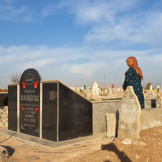 En kvinne i Syria står ved graven til en kvinne født i 1993, død 2020.