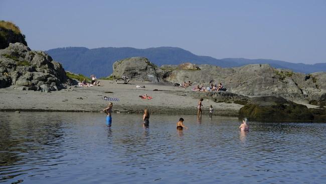 Bading i Korsvika tidlig mandag morgen. Vi ser seks personer i vannet, og flere som soler seg på stranda.