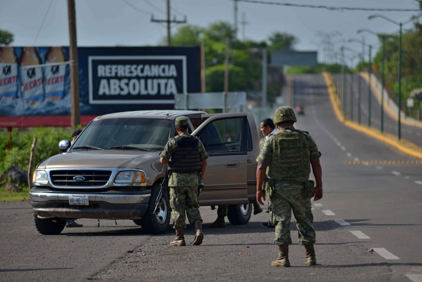 Soldater kontrollerer en bil på motorveien mellom Guzmans hjemby, Badiraguato, og Santiago de Los Caballeros i Sinaloa.