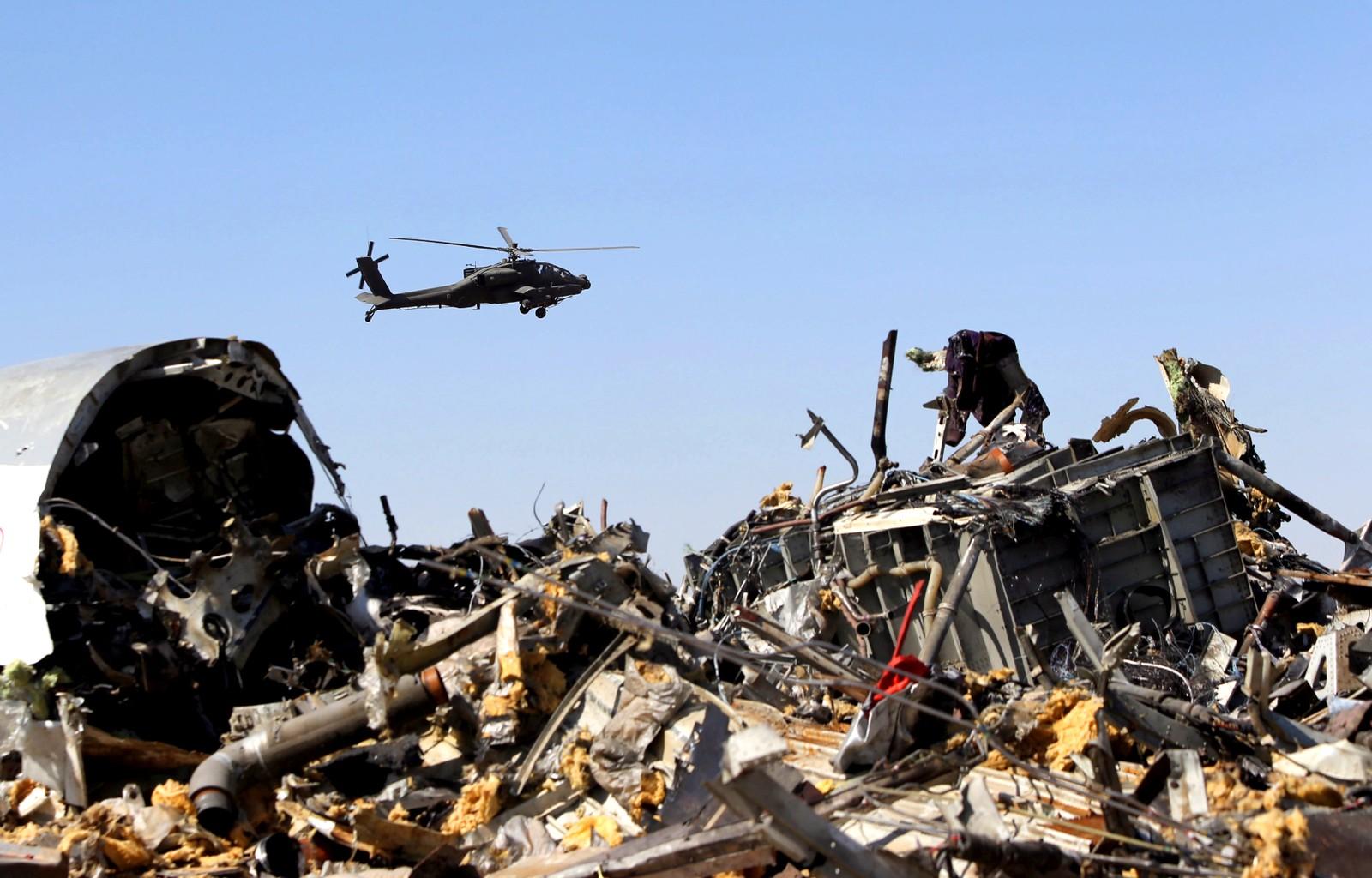 Et militærhelikopter flyr over vraket til det russiske passasjerflyet.