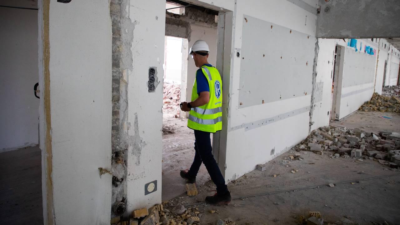 Vi ser ryggen på Svein Egil Dagsland i refleksvest og med vernehjelm, på vei fra ett tomt rom inn i et annet. Bare betongveggene står igjen. På bakken ligger det resten av ødelagt murstein.