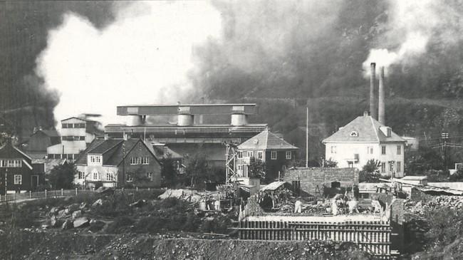 Høyanger på 1930-talet. Ikkje fritt for at det kom litt røyk opp frå verket. Foto: Eugene Nordahl-Olsen. Eigar: Hydro/Fylkesarkivet i Sogn og Fjordane.