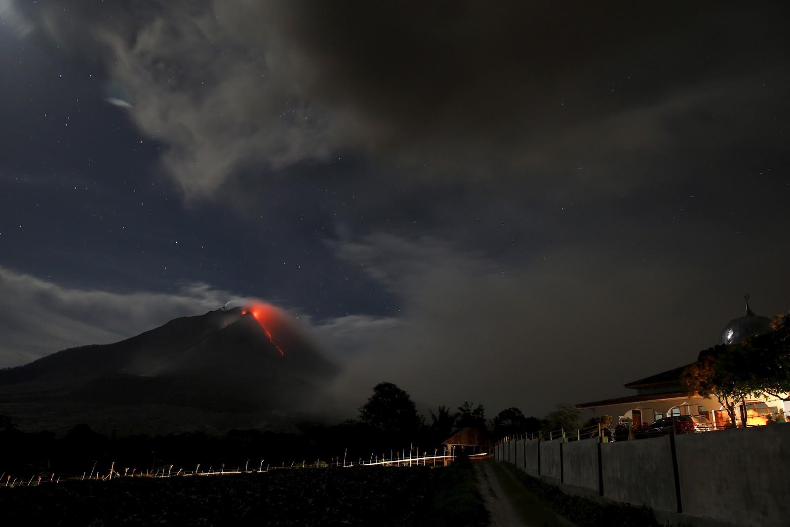 Varm lava renner fra vulkanen Mount Sinabung i Indonesia 24. juni. Bildet er tatt fra byen Tiga Serankai i provinsen Nord-Sumatra.