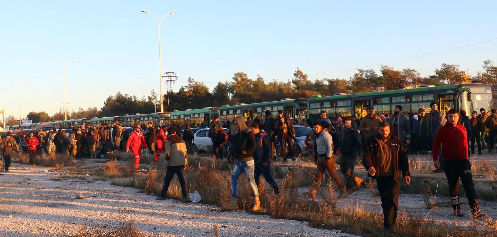 Evakuerte går av bussen i al-Rashideen.