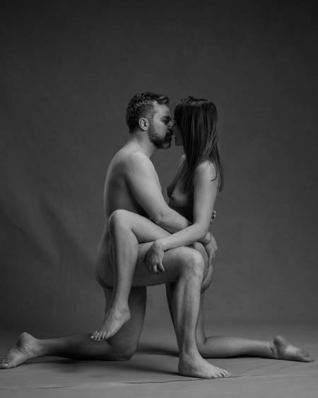 En naken mann med mørkt hår og skjegg og en naken dame med langt brunt hår siter med ett kne på gulvet og det andre kneet over den andres lår