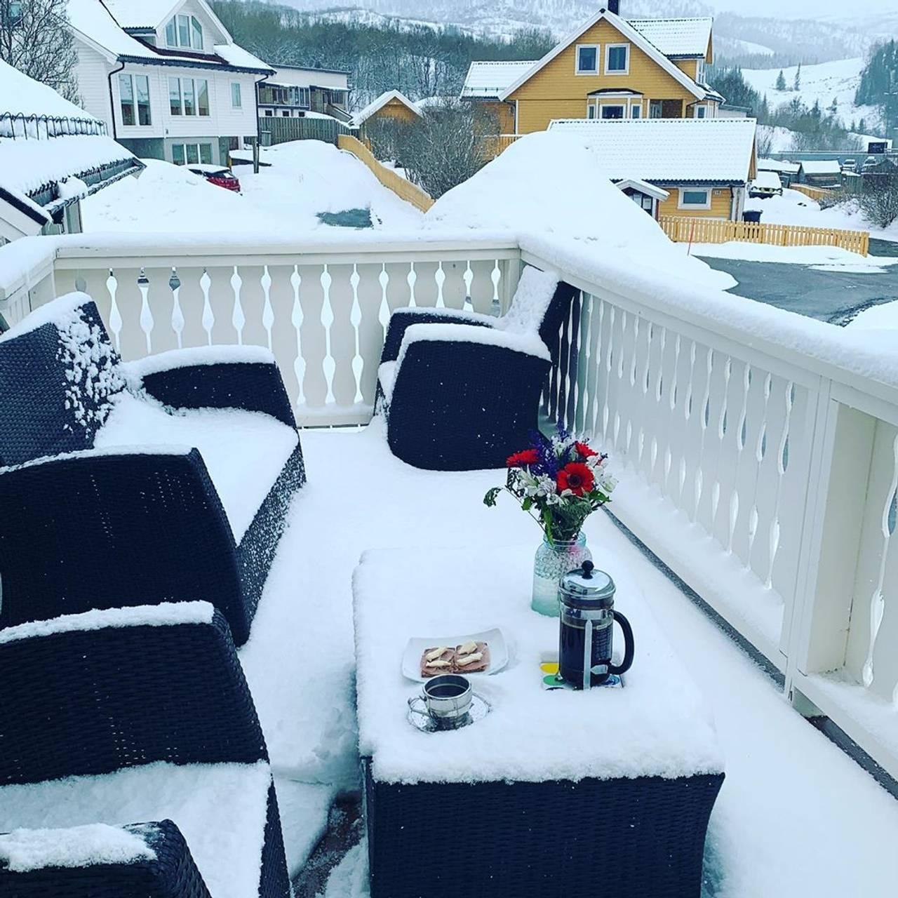 Her er det rigget til frokost på verandaen. Men hagemøblene er dekket i snø.