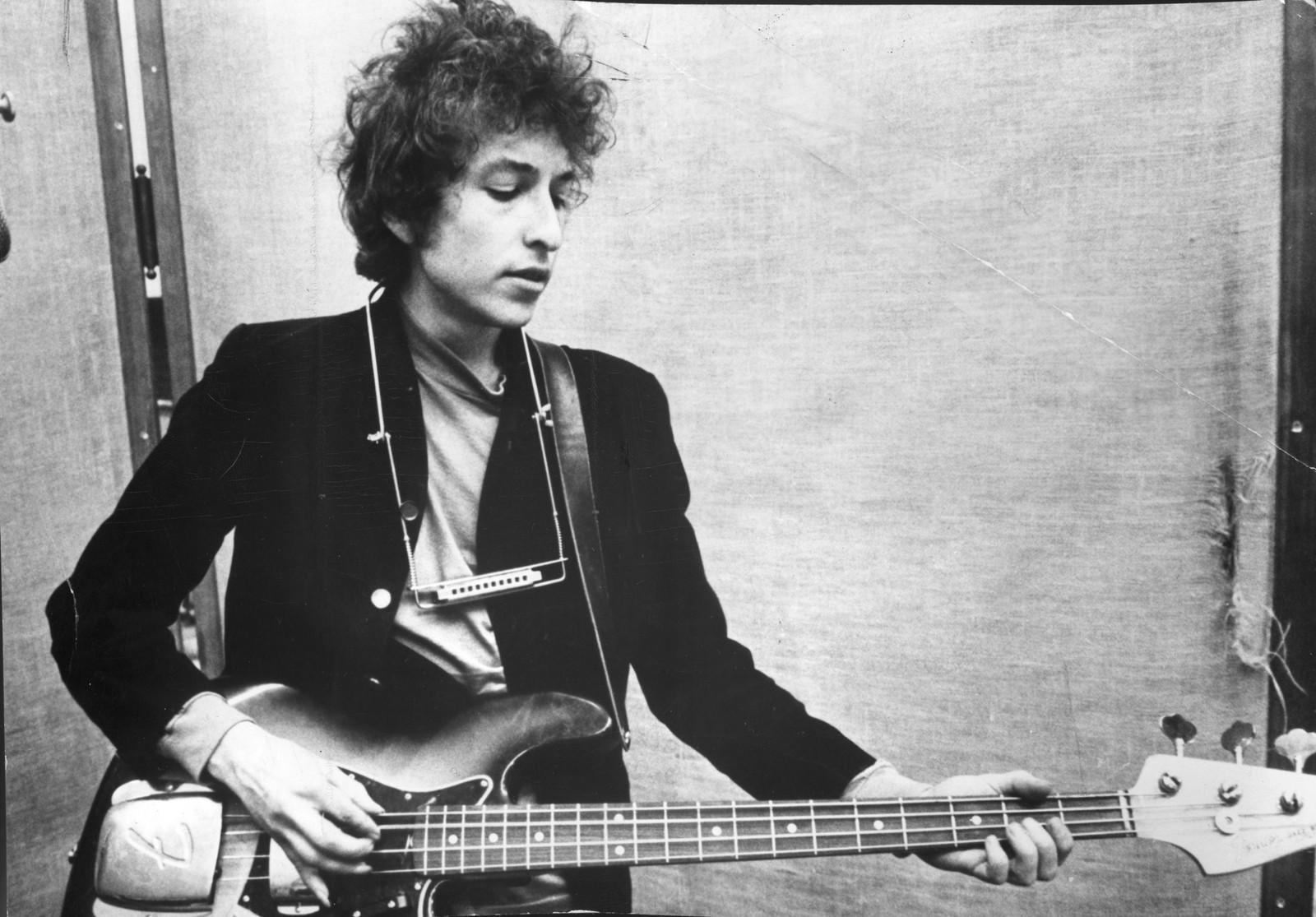 Et tidlig bilde av Bob Dylan som spiller bassgitar.