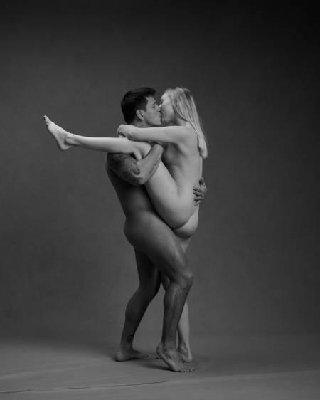 En naken dame står på det ene benet med det andre benet over skulderen på en naken mann hun kysser