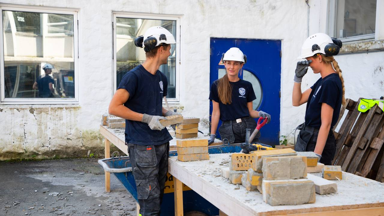 De tre sommervikarene står ute rundt et arbeidsbord. De er kledd i arbeidstøy, med hansker, hjelm og hørselsvern. På bordet ligger det murstein som skal pusses.