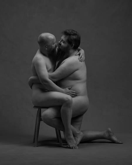 En naken mann med skjegg sitter på en krakk mens han holder rundt en annen naken mann som står på kne inntil ham