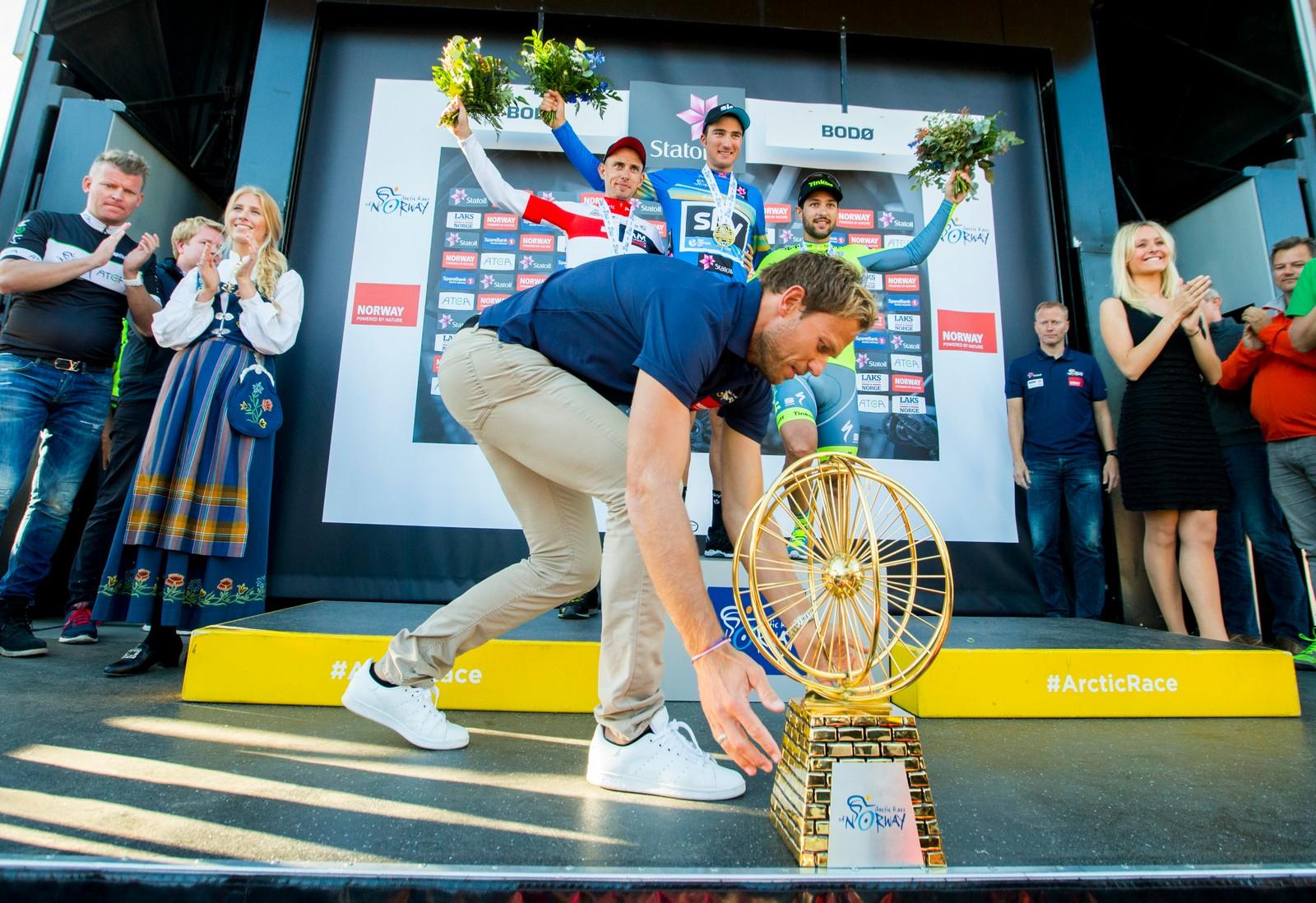 Thor Hushovd, ambassadør og tidligere vinner av Arctic Race of Norway, plukker opp sammenlagttrofeet for å gi det til Gianni Moscon fra Italia (Team Sky) etter fjerde og siste etappe i sykkelrittet Arctic Race of Norway søndag. Stef Clement (IAM) kom på 2.-plass, mens Oscar Gatto (Tinkoff) kom på 3.-plass.