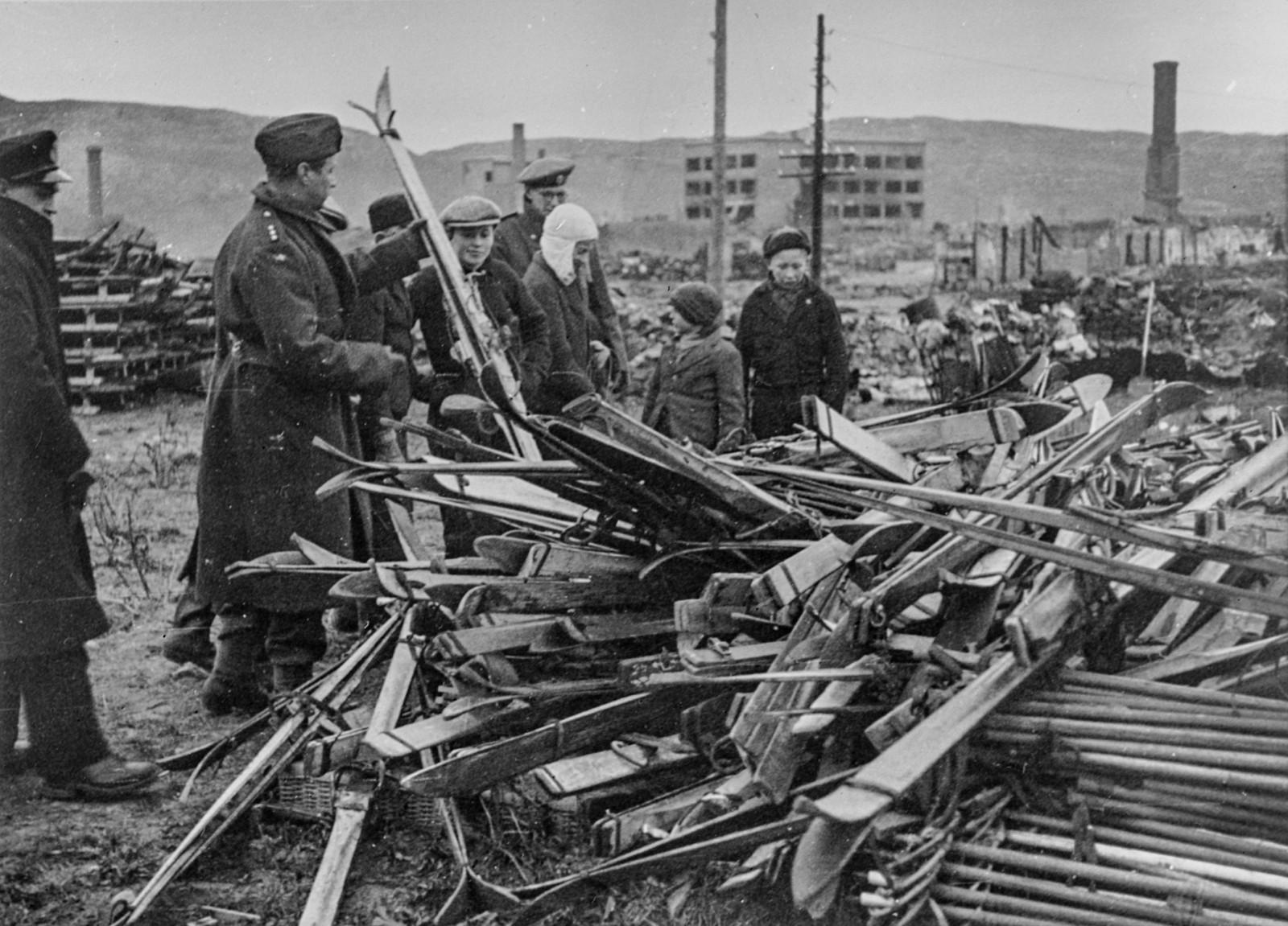 Original bildetekst: Småbyene og fiskeværene i Nord-Norge ligger som ødeleggelsens monumenter over tysk mordpolitikk, med husene i ruiner og skorsteinspipene stikkende opp mot himlen. I Kirkenes var ødeleggelsen nesten total, bare 28 hus sto tilbake. I Vadsø var 65-70% av byen ødelagt og i Vardø 85%. Innover Varangerfjorden til Vest-Tana er det nesten intet igjen. - Dette lager av ski som sees på bildet rakk tyskerne imidlertid ikke hverken å få ødelagt eller å få med seg. Utstyret studeres av norske offiserer for å bringe på det rene om det kan tas i bruk av troppene.
