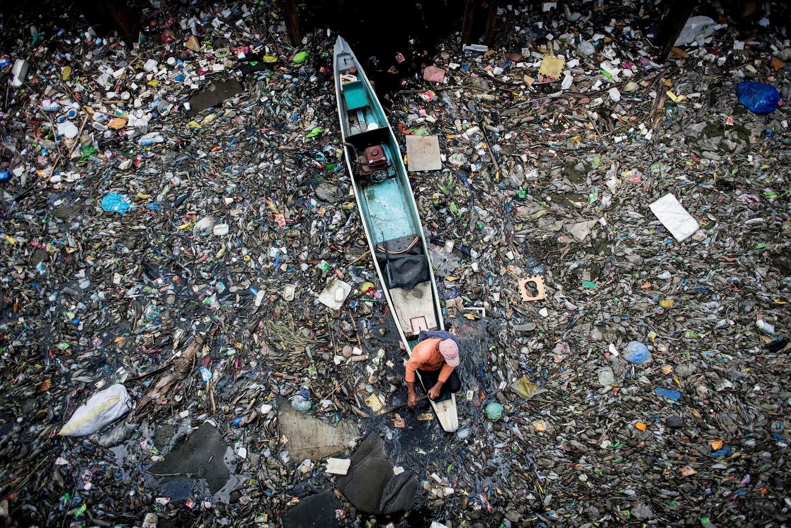 En arbeider fjerner søppel fra Marilao-elva i Bulacan på Filippinene. Elva ble i 2007 kåret til å være en av de 30 skitneste stedene i verden.