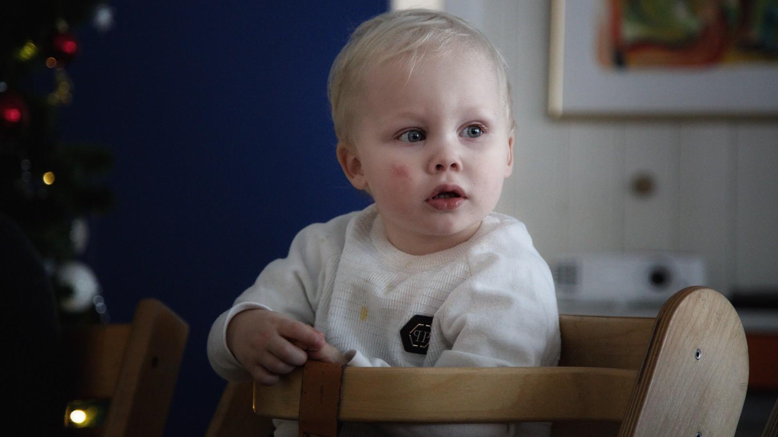 En lyshåret liten gutt holder noen i handa. Gutten smiler og er på vei fra høyre mot venstre inne i et rom.