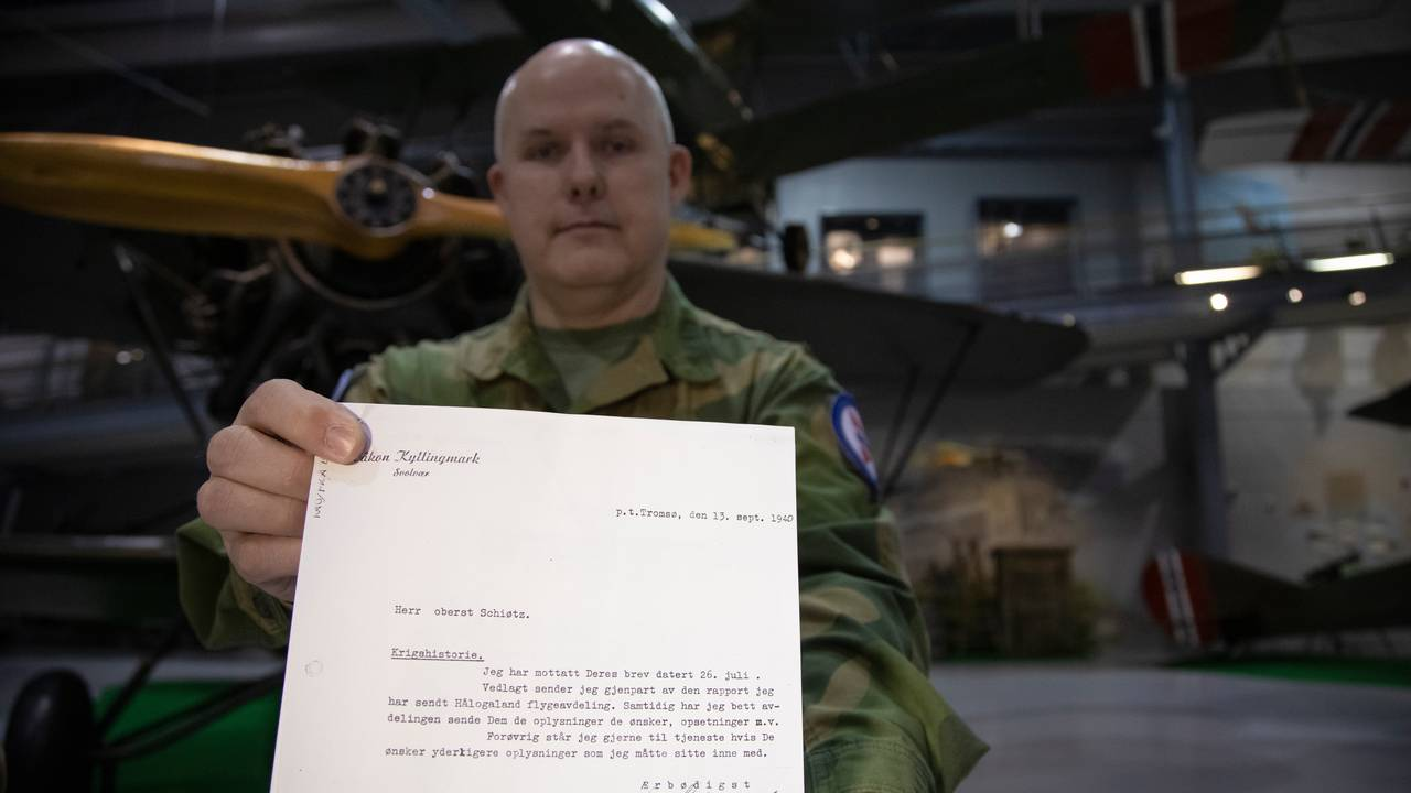 Anders Utgård holder fram rapporten som er overlevert Luftforsvarmuseet i Bodø.