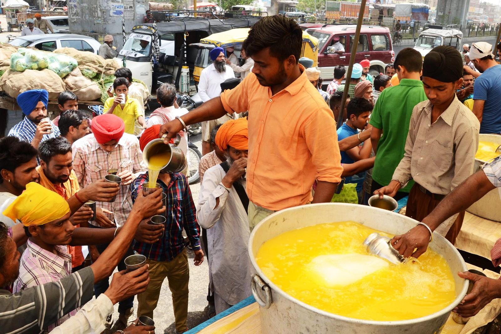 En frivillig deler ut avkjølt saft til tørste forbipasserende i Amritsar.