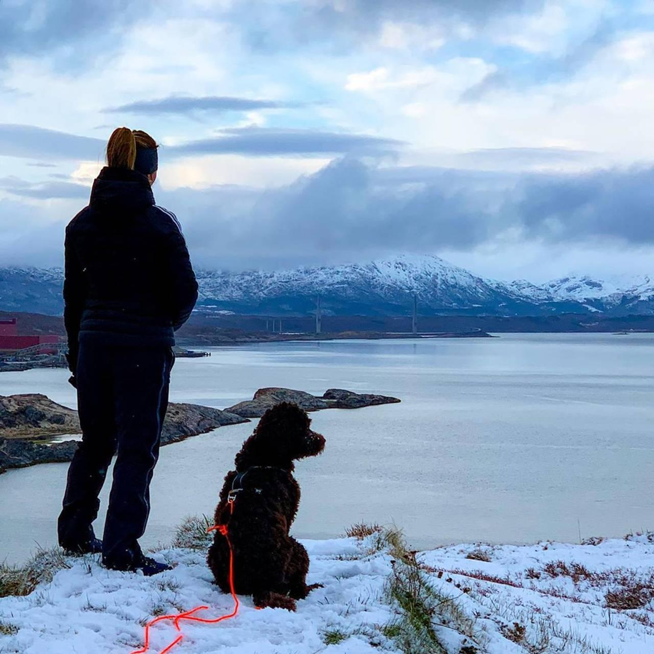 Eier og hund står på snødekt underlag og ser utover sjøen.