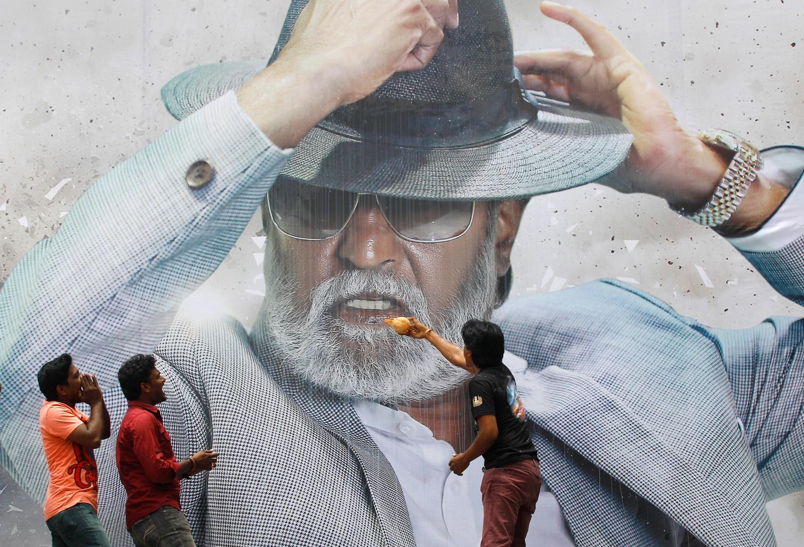 """Tilhengere av den indiske superstjernen Rajinikanth hyller skuespilleren foran en plakat utenfor en kino i Chennai i India den 22. juli. Under visningen av filmen """"Kabali"""" skal publikum i Malyasia og India ha hoppet i setene og danset på gulvet mens helten bekjempet fiender i gangsterfilmen."""