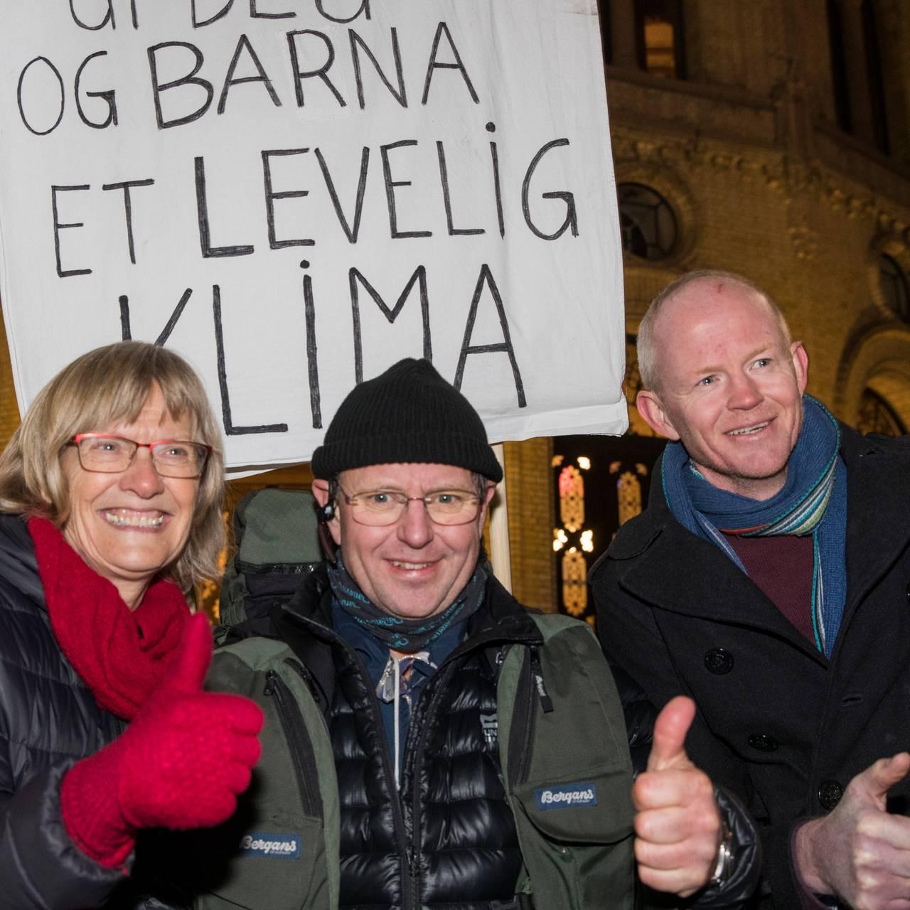 Karin Andersen, Thomas Cottis og Lars Haltbrekken utenfor Stortinget med plakat med budskap om å redde klima.