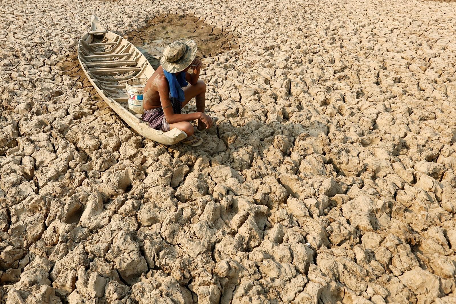 En fisker tar seg en røyk på en båt i det som var en innsjø i Kambodsja. El Niño skal ha ført til en tørkeperiode landet ikke har opplevd på 50 år. Flere hundre tusen mennesker står i fare for å gå tomme for rent vann.