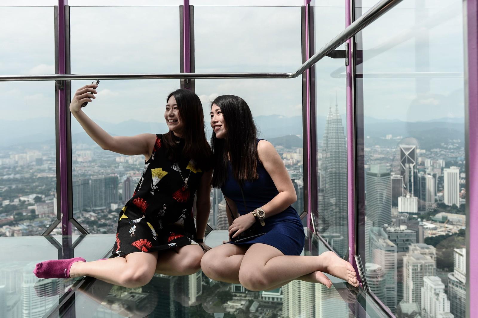 """Ng Sin Nee og Lee Shin May fra Malaysia tar en selfie fra Sky Box i KL Tower. """"Boksen"""" åpnet for turister 20 mai og har blitt en attraksjon. Det er plass til seks mennesker uten høydeskrekk om gangen. """"Boksen"""" er 300 meter over bakken i Kuala Lumpur."""