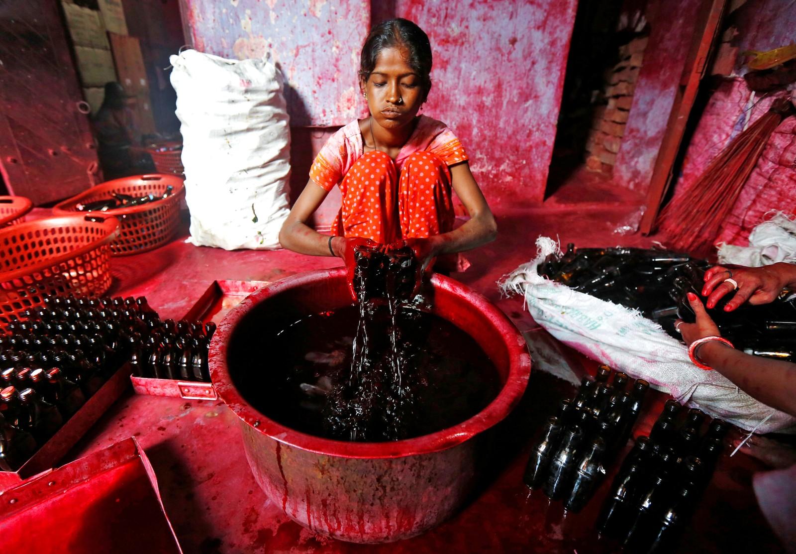 En arbeider fyller flasker med alta den 2. august i Kolkata i India. Alta er et rødt fargestoff som hindukvinner smører på føttene under bryllup og religiøse tilstelninger.