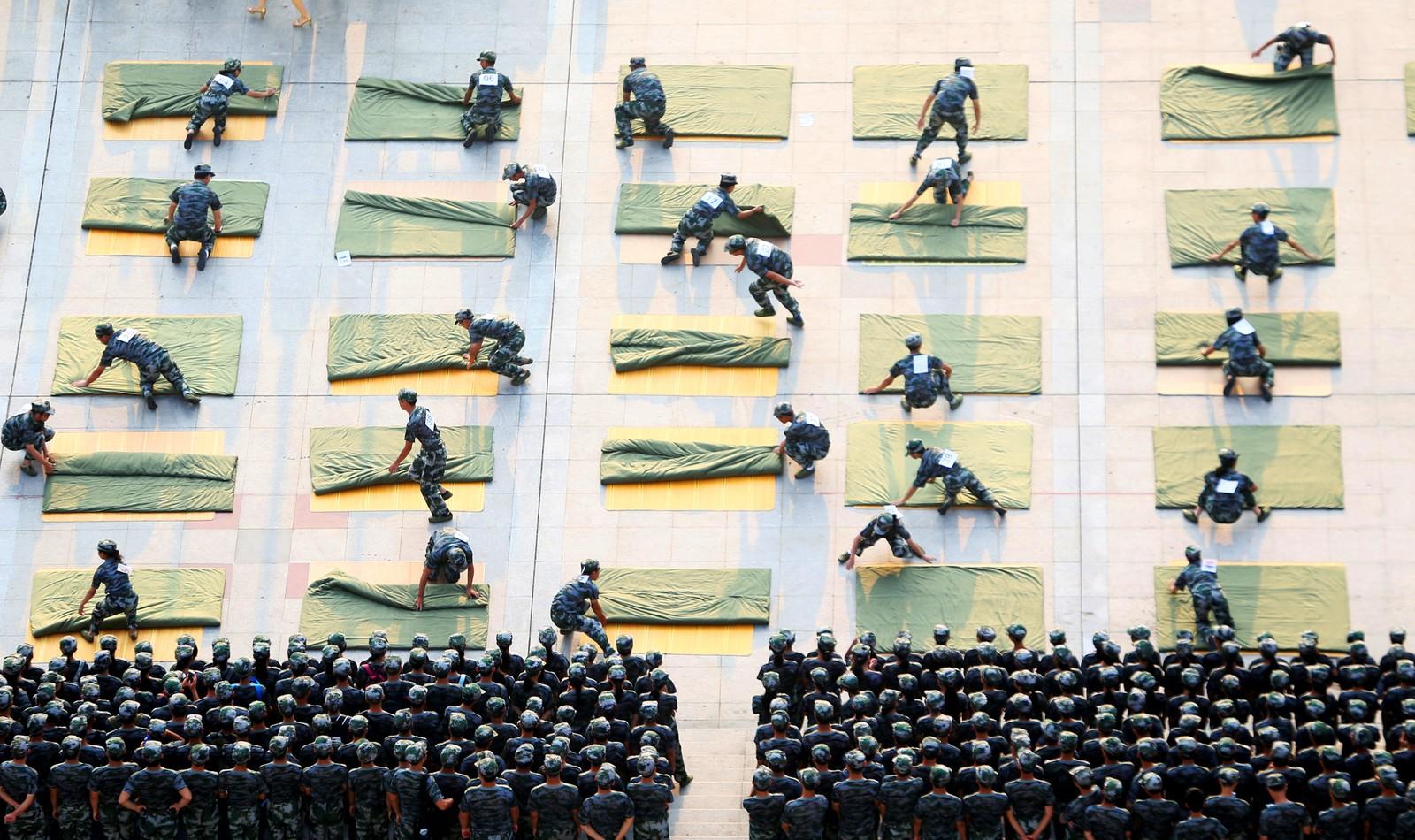 Universitetsstudenter konkurrerer om hvem som er raskest til å brette sengetepper under en militær treningsøvelse ved begynnelsen av semesteret i Hengyang i Kina den 8. september.