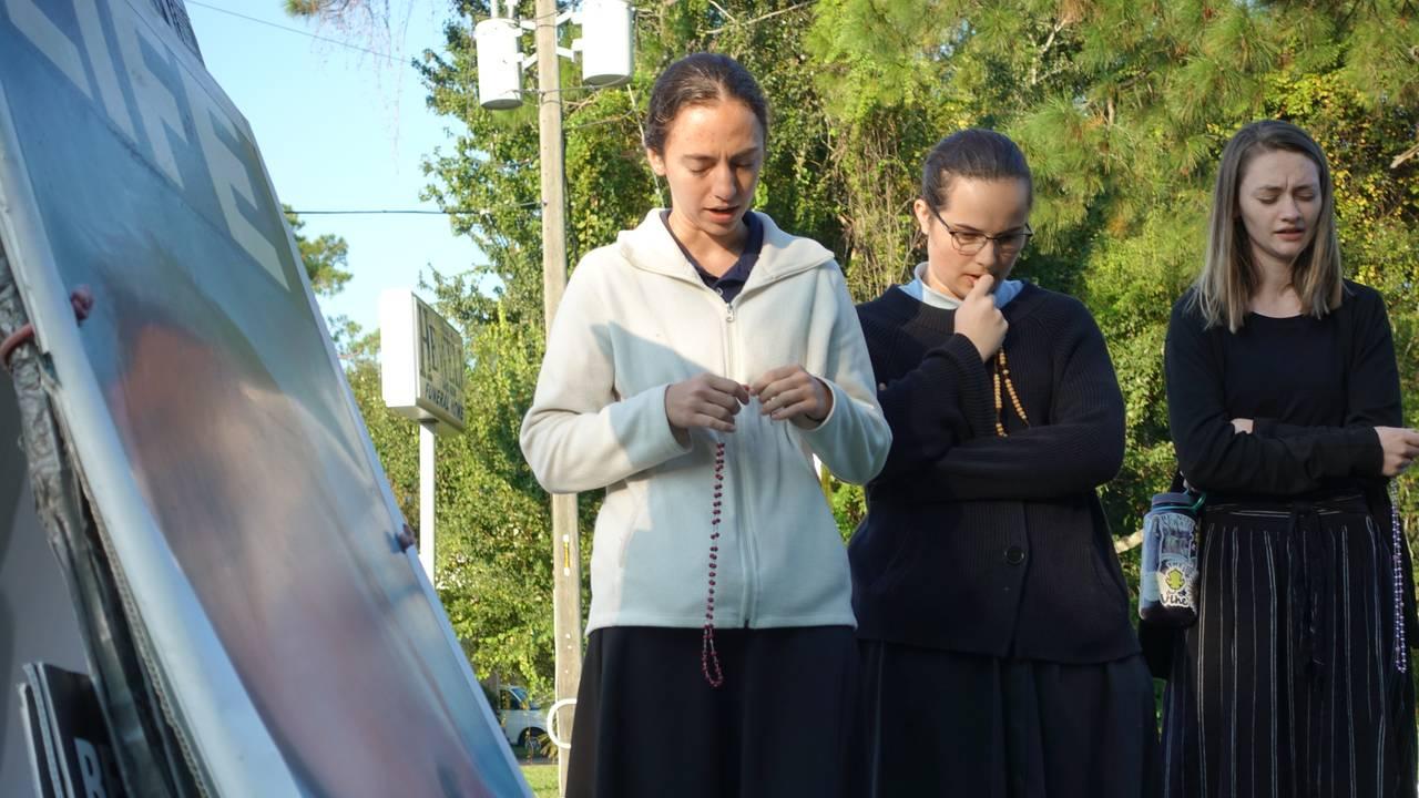 BER FOR FORBUD: Nancy McAndrew (22) (t.v), Hayden (18) og Lexi (18) samles til bønn foran abortklinikken. De går alle på katolsk skole i Florida.