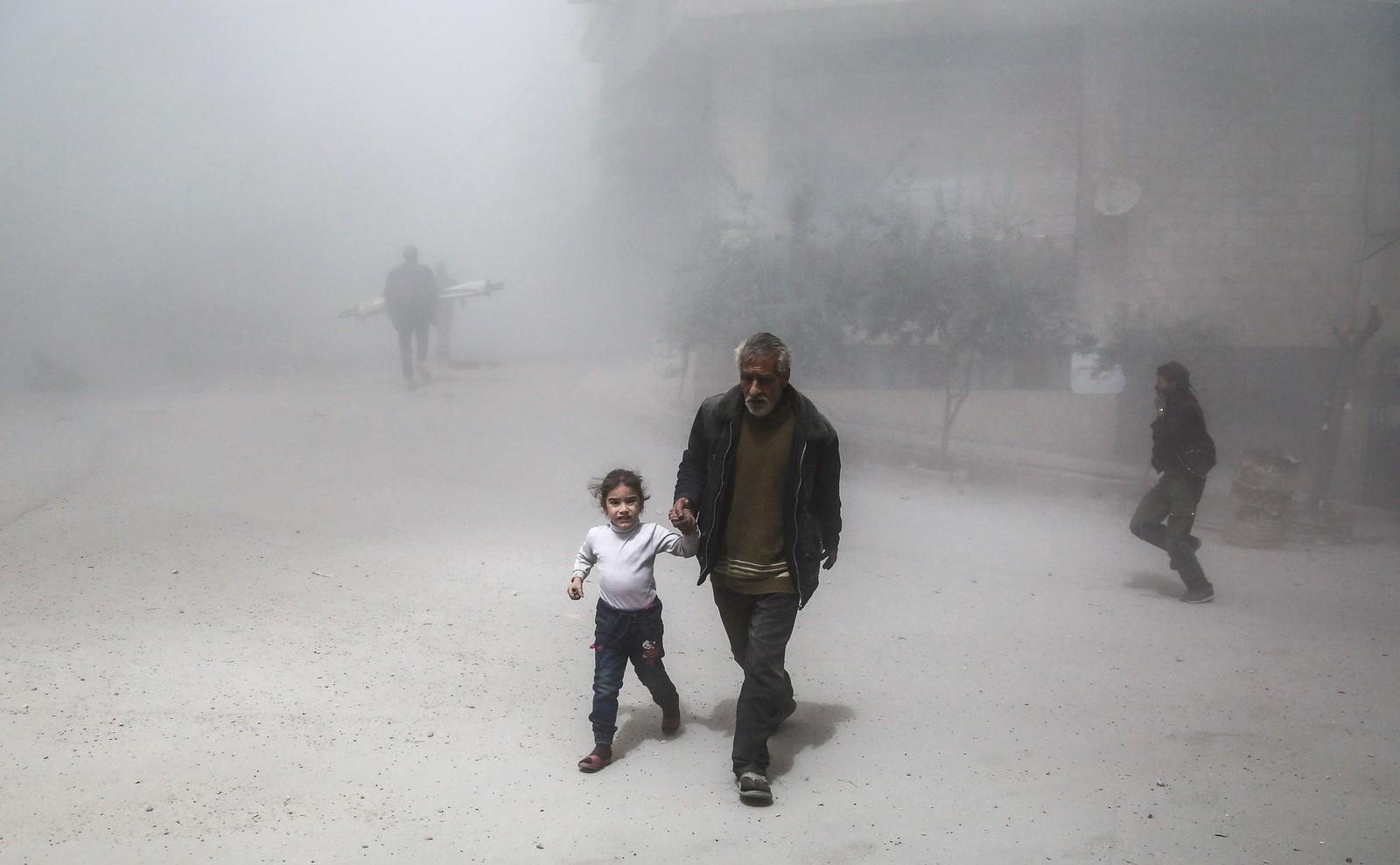 En syrisk mann og en jente forsøker å komme seg i sikkerhet etter et luftangrep mot byen Hamouriyah i Syria.