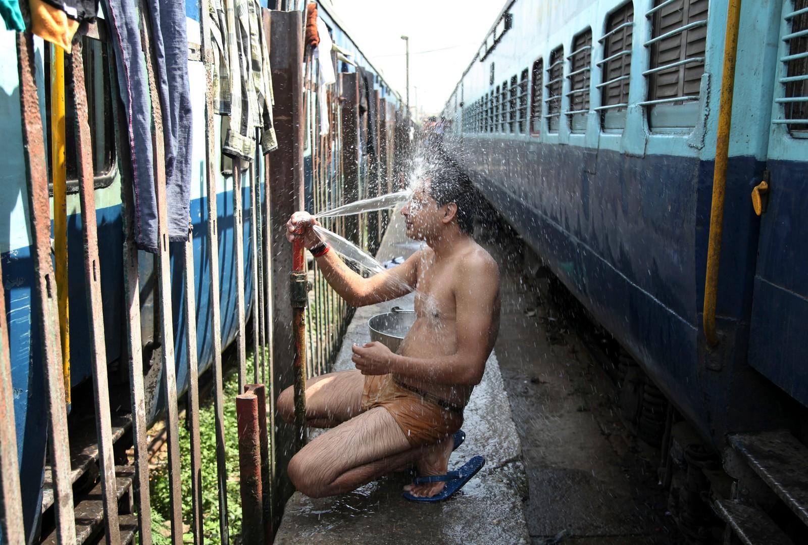 En reisende kjøler seg ned ved jernbaneskinnene i Jammu, India.