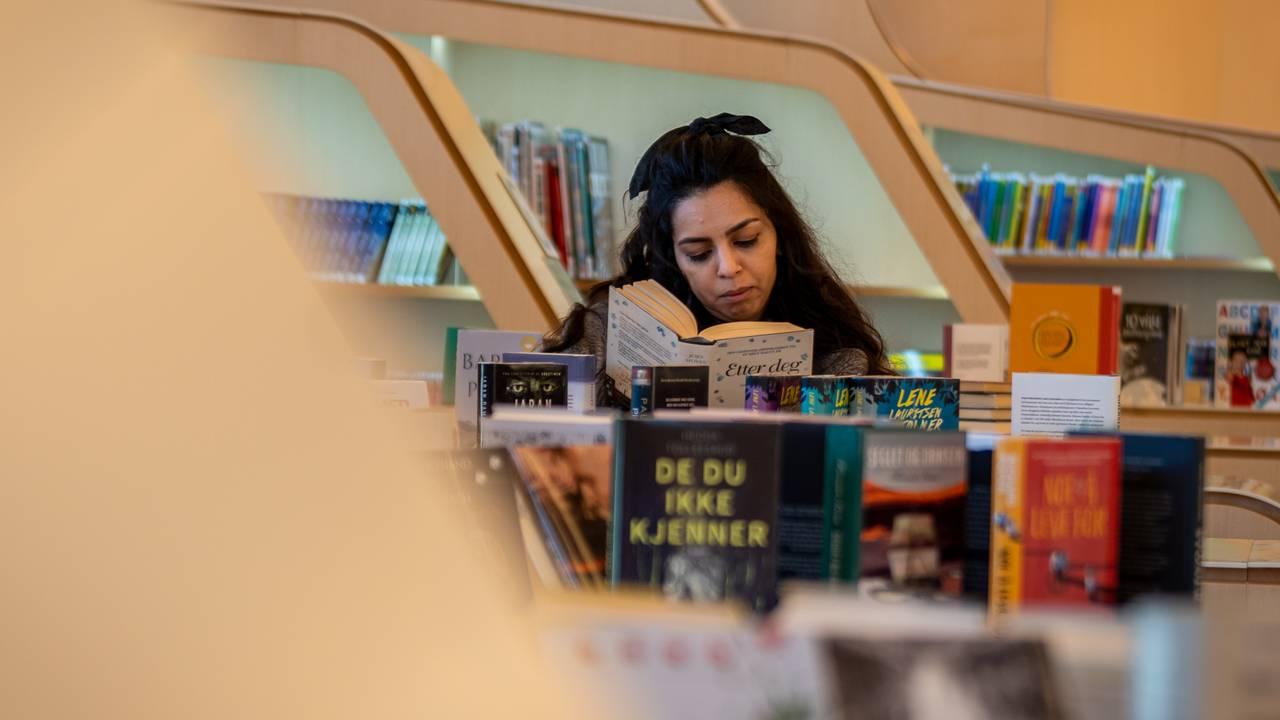 Cristina Berki leser i en bok på biblioteket i Vennesla
