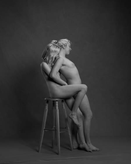 En naken dame sitter oppå en høy krakk og kysser en annen naken dame i nakken som står mellom bena hennes