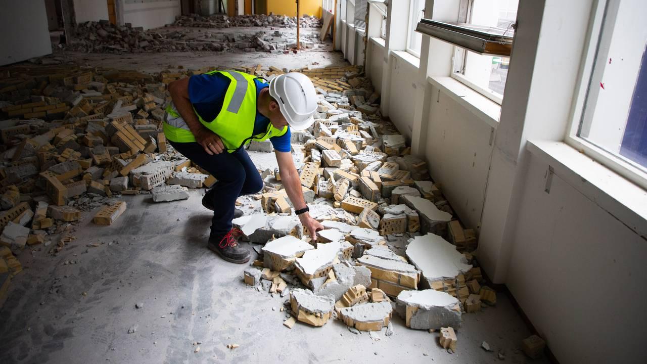 Svein Egil Dagsland bøyer seg for å plukke opp en murstein. På gulvet ligger det resten av mursteinsveggene som er revet.