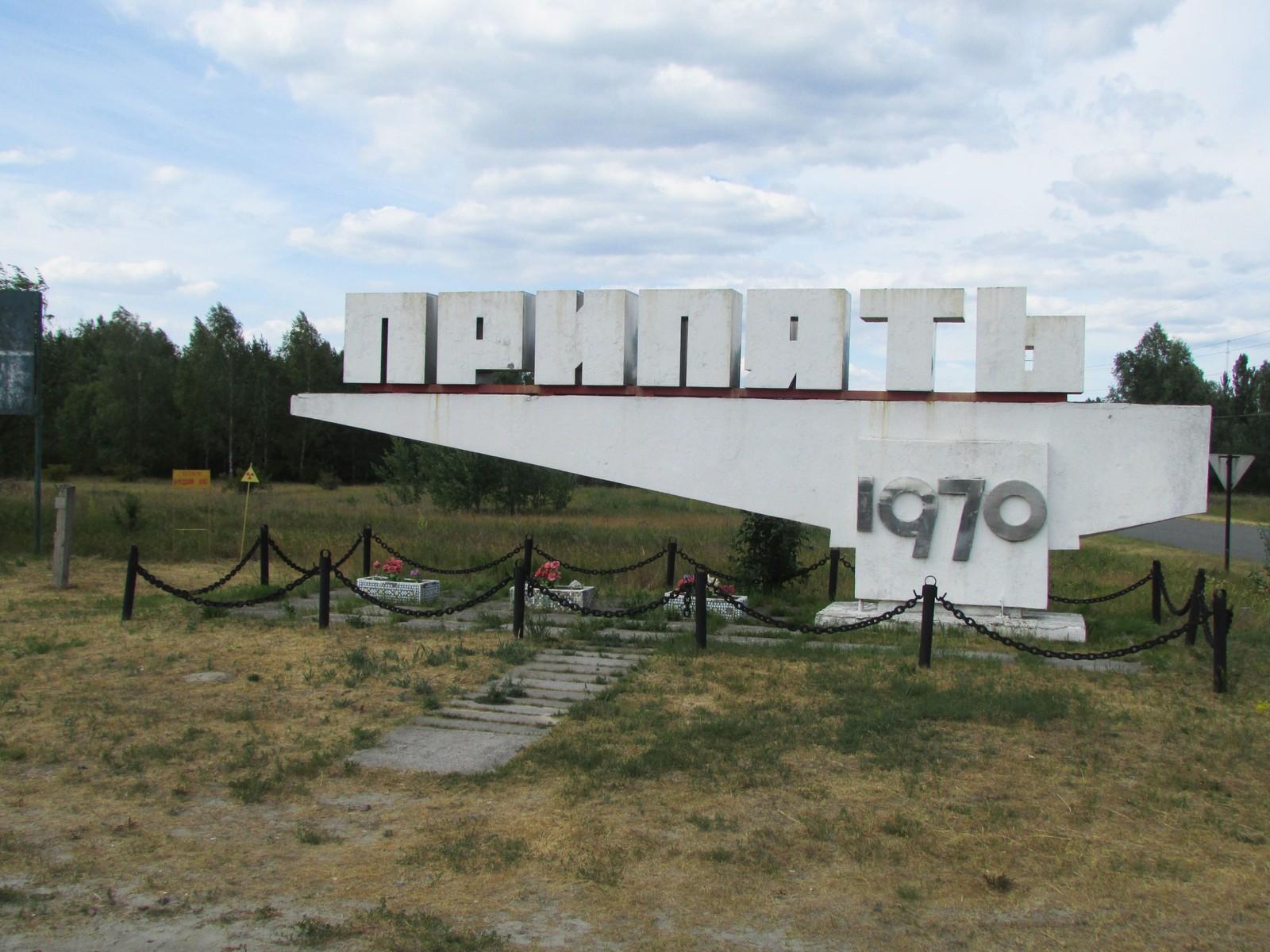 Skiltet som viser hvor Pripyat by ligger. Legg merke til skiltene som advarer mot radioaktivitet. På den ene skiltet står det «Rød skog».
