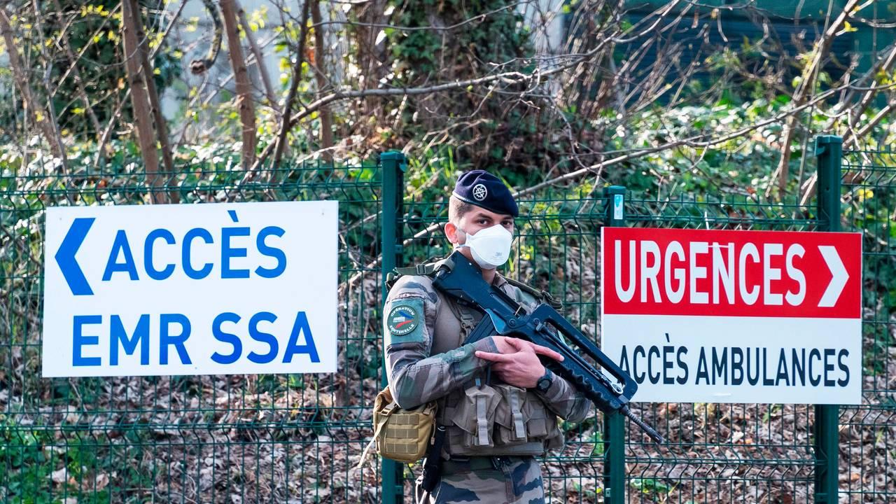 Bevæpnet franske militære holder vakt utenfor et militært felthospital som er satt opp utenfor Mulhouse for å ta hånd om de mange syke.