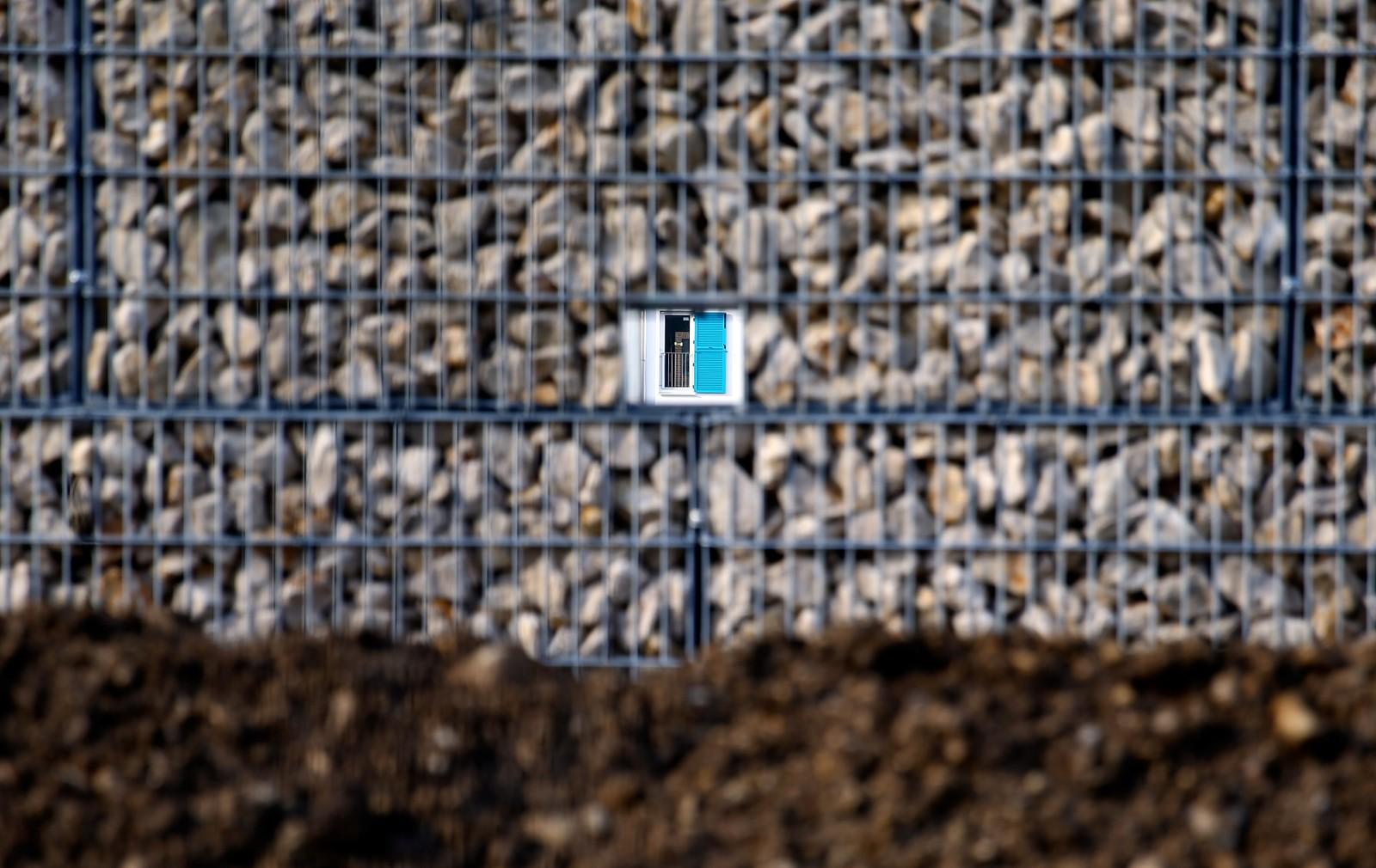 Et vindu ved et asylmottak sett gjennom et hull i et steingjerde utenfor München i Tyskland. Den fire meter høye muren er satt opp for å holde asylsøkerne adskilt fra øvrige beboere i nabolaget.