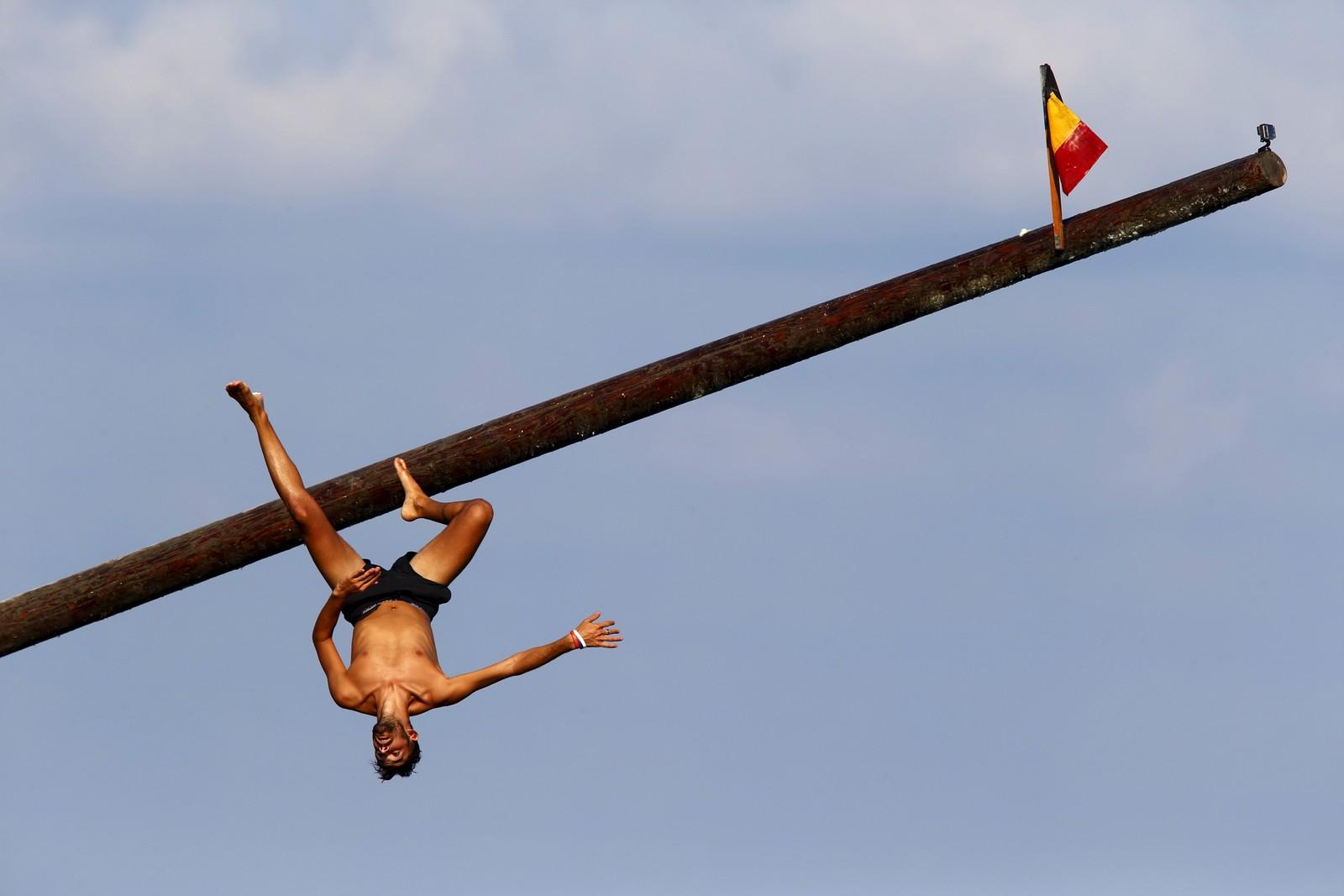 En mann faller mot havet idet han prøver å løpe til topps på den oljeinnsmurte pålen under konkurransen Gostra. Den som klarer å fange flagget vinner konkurransen. Arrangementet er en del av den årlige festivalen St. Julian, som finner sted på Malta.