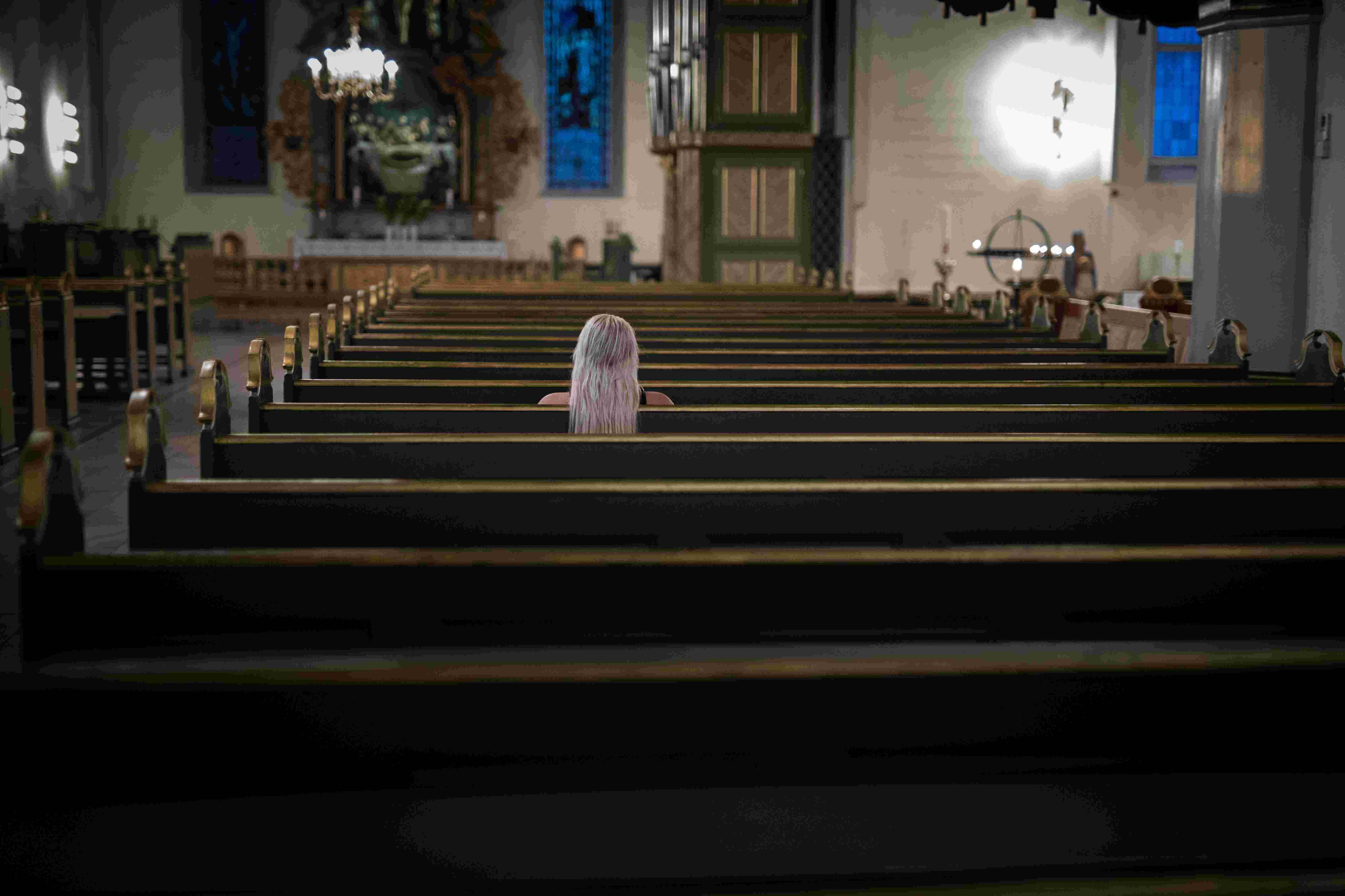 Jente sitter alene i kirkebenk