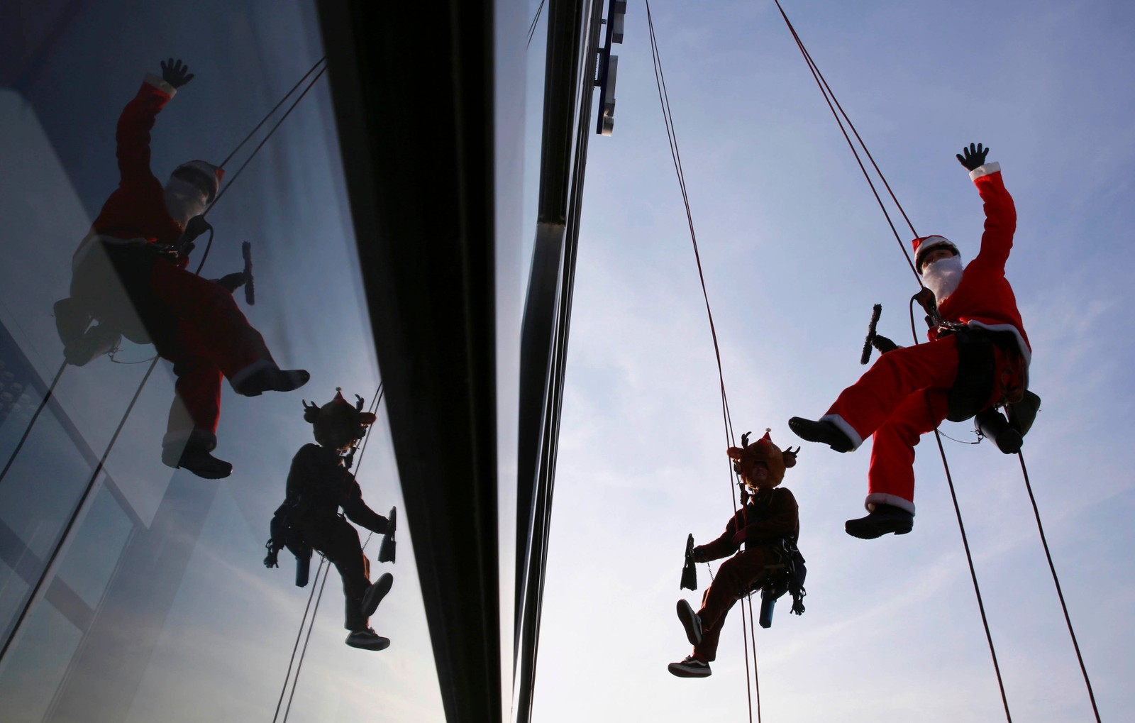 Disse vindusvaskerne har kledd seg ut som julenissen og reinsdyret Rudolf i Tokyo i Japan.