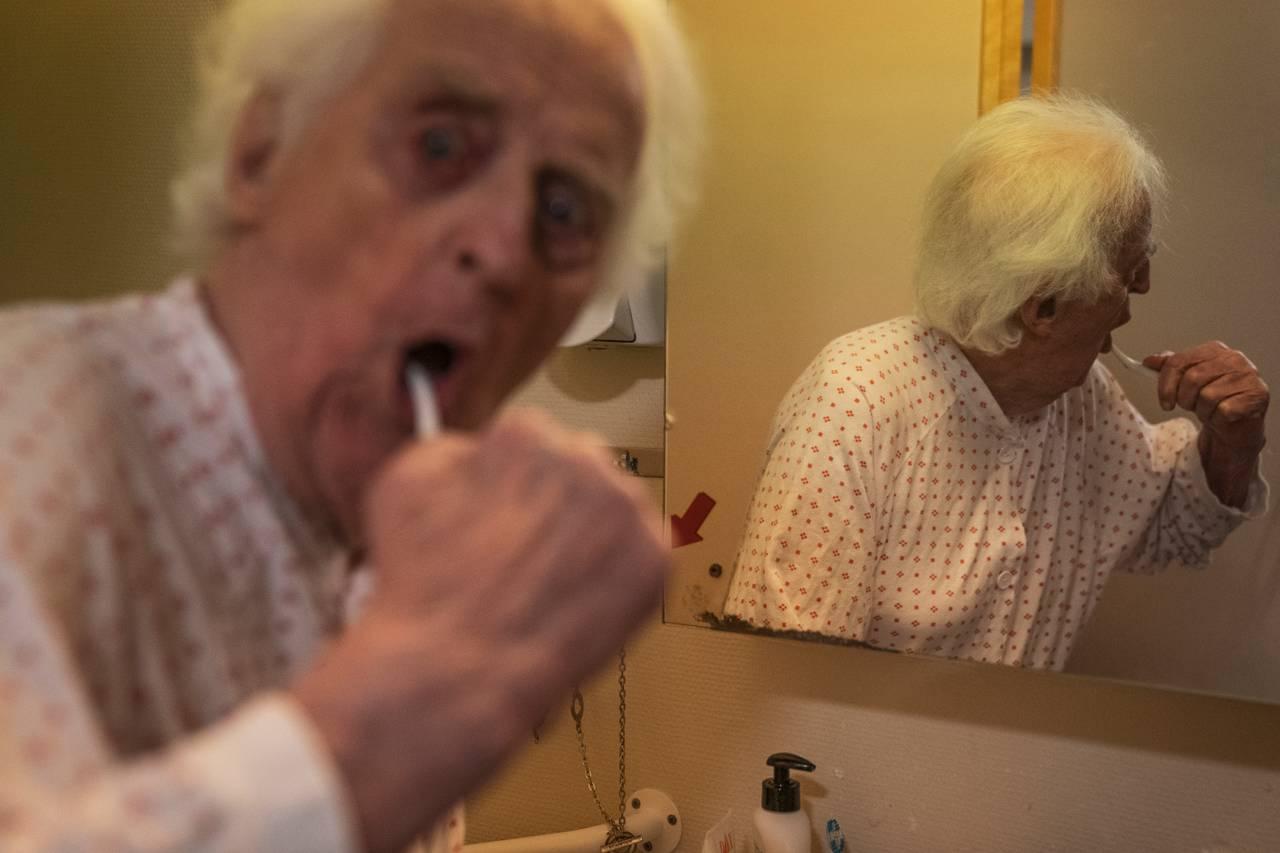 Birger pusser tennene i speilet og ser bak seg mens han pusser