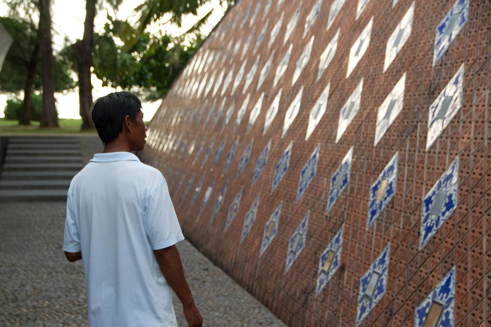 Han ser på minneveggen som står i Nam Khem Memorialpark. Navnet til sønnen er skrevet her.