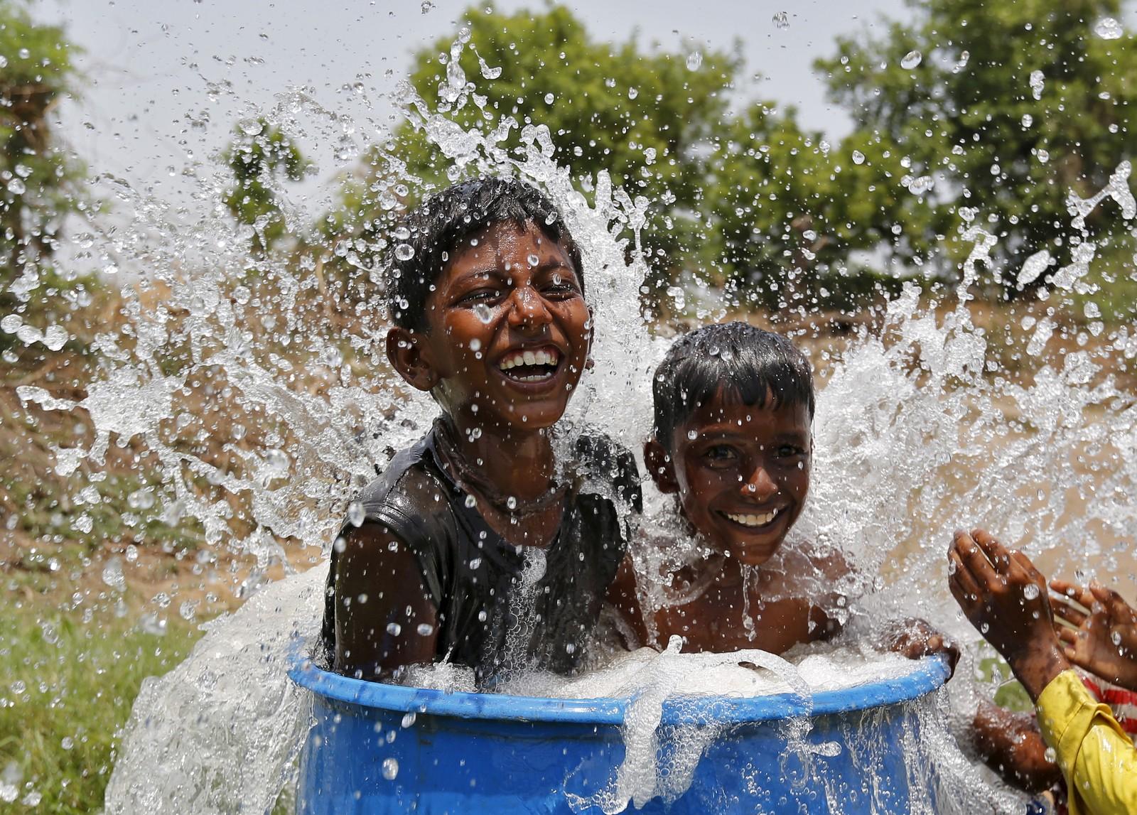 Barn kjøler seg ned med vann i indisk hetebølge.